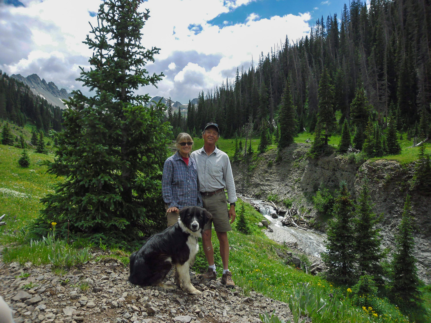 Ed & Lyn Keese in the mountains of Colorado with their dog near a stream