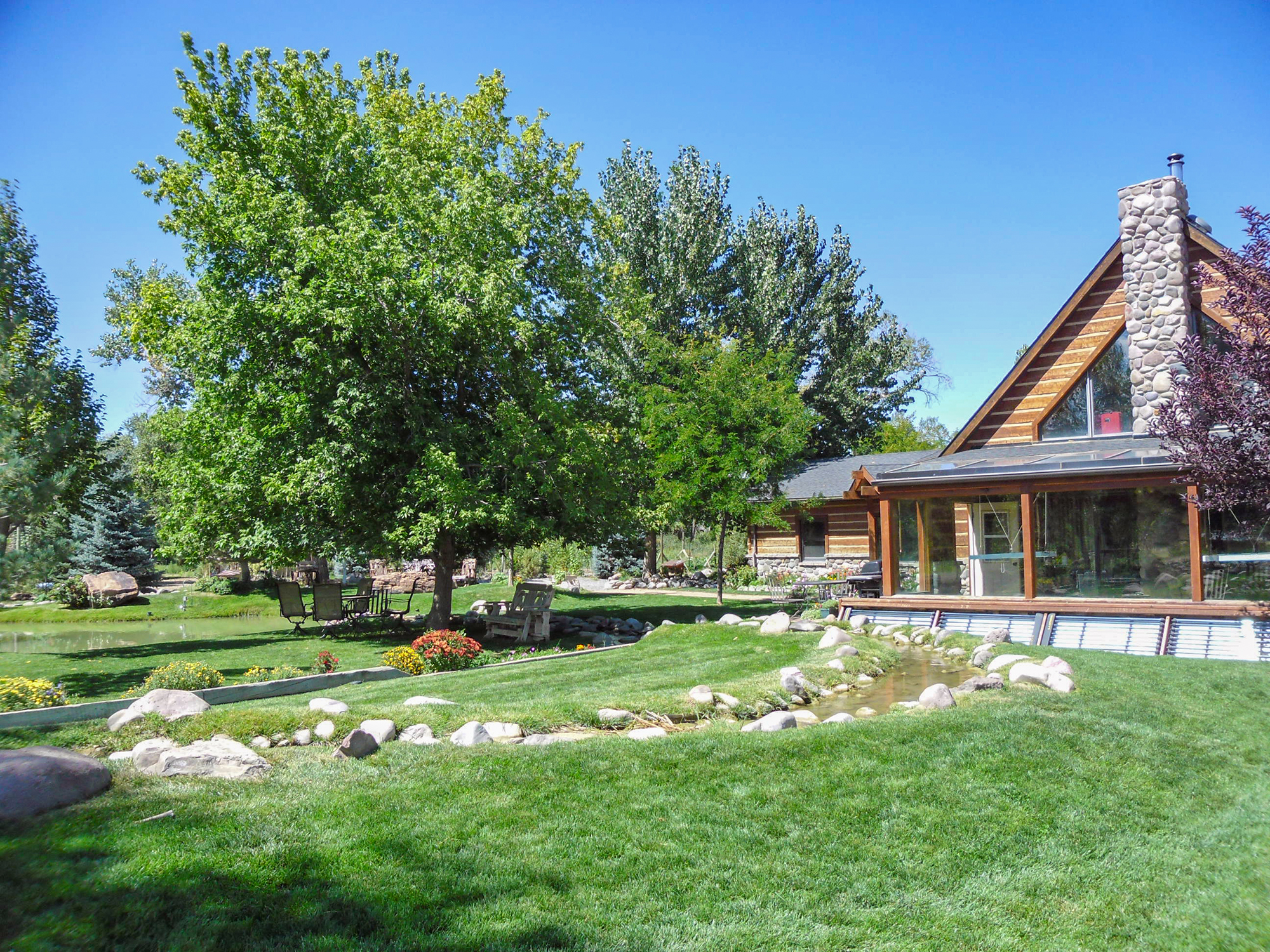 log and stone home with a stream and landscaping from Beaver Lakes Nursery & Landscape Supply