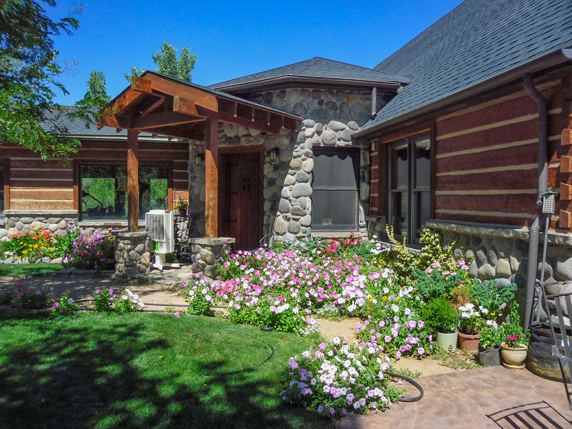 log and stone home with lots of flowers in Montrose, Colorado